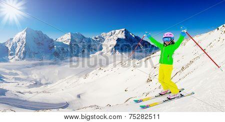 Skiing, skier on ski run - happy girl skiing downhill