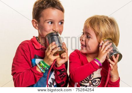 two small children are talking to an telephone of two doses.