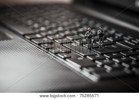 Miniature Swat Squad Protecting Laptop Computer. Technology Concept