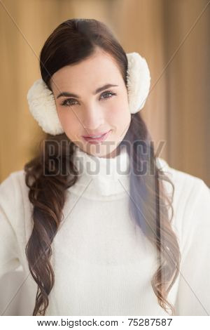 Pretty brunette with ear muffs smiling at camera at home in the living room