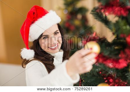 Happy brunette decorating a christmas tree at home in the living room