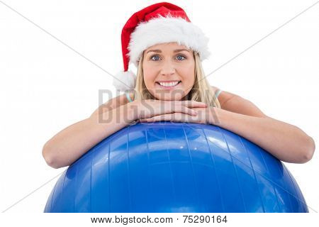 Festive fit blonde leaning on exercise ball on white background