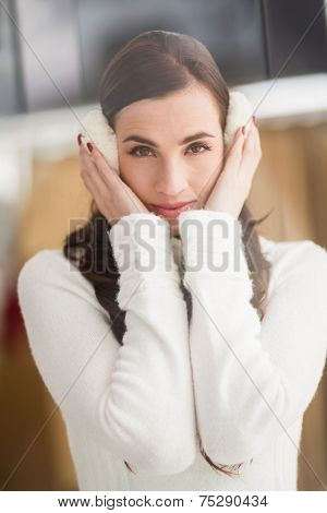 Pretty brunette with ear muffs at home