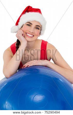Festive fit brunette leaning on exercise ball on white background