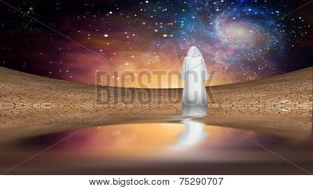Desert and galactic sky with wandering cloaked figure Elements of this image furnished by NASA