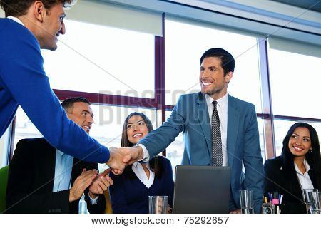 Business people sitting at the table while two of them shaking hands