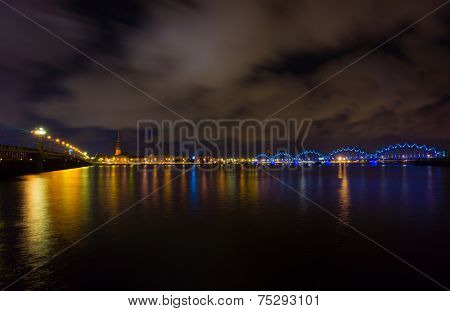 Night landscape of Daugava river, old town and railway bridge at night in Riga, Latvia