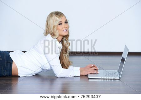 Young woman lying her stomach on the bare floor with a laptop turning to smile at the camera  with copyspace