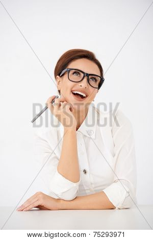 Laughing attractive young woman wearing glasses looking up into the air as she sits at a table  over white