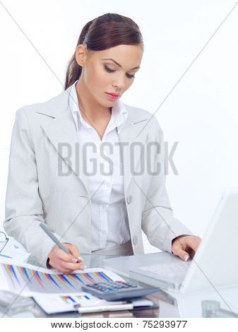 Elegant businesswoman working at her desk writing notes as she researches information on her laptop