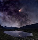 stock photo of comet  - Night landscape with mountain lake and bright comet reflected in it - JPG