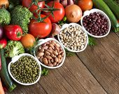 stock photo of legume  - Legumes in bowls and vegetables on a wooden table - JPG