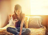 stock photo of crossed legs  - tech savvy asian teen girl using smart phone in bed room - JPG