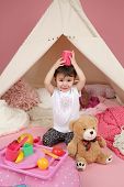 stock photo of teepee  - Toddler child kid engaged in pretend play with food stuffed toys and teepee tent - JPG