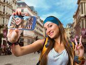 stock photo of flirty  - Happy traveler woman is taking selfie - JPG