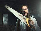image of witch-doctor  - Scary portrait of an angry woman with a saw - JPG
