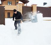 pic of snow shovel  - Man cleans snow shoveling around the house - JPG