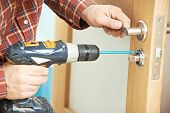 image of carpenter  - carpenter at lock installation with electric drill into interior wood door - JPG