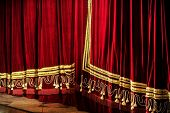 stock photo of curtain  - Side view with a closed opera red velvet curtain - JPG