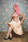 image of freaky  - Freaky young woman in vintage corset sitting on chair with white rabbit on her knees - JPG