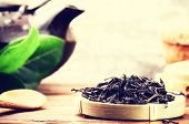 stock photo of teapot  - Closeup of loose black tea and teapot - JPG