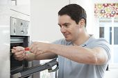 picture of oven  - Repairman Fixing Faulty Domestic Oven In Kitchen - JPG