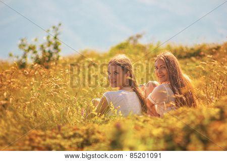 Girls sit in grass