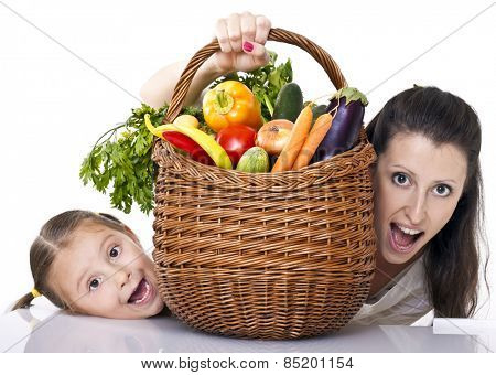 Mom and kid fun in kitchen with basket full of vegetables