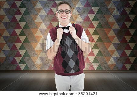 Geeky hipster fixing his bow tie against orange background with vignette