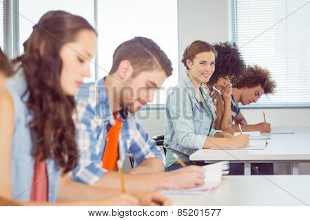 Fashion student smiling at camera in class at the college