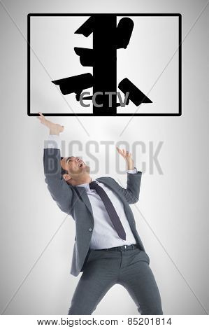 Stressed businessman with arms raised against cctv
