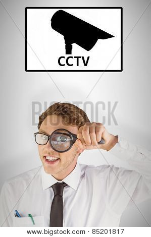 Geeky businessman looking through magnifying glass against cctv