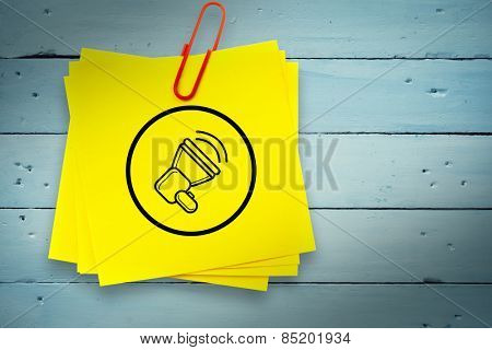 Megaphone graphic against sticky note with red paperclip