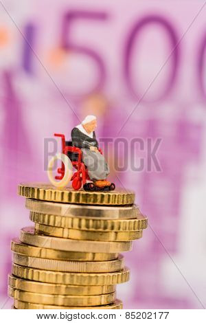woman in wheelchair on money stack symbol photo for disability care allowance and costs public health