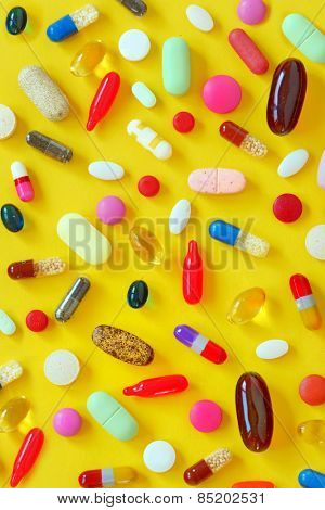 Many colorful pills on yellow background