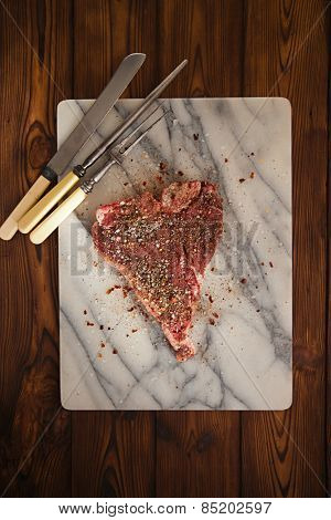 beef steak t-bone with vintage meat fork on marble backdrop