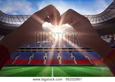 Woman making heart shape with hands against stadium full of russia football fans