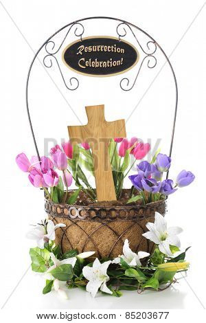 A basket containing a wooden cross and surrounded by colorful tulips.  It's surrounded by Easter lilies and the handle contains a sign saying,