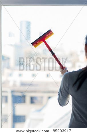 people, housework and housekeeping concept -close up of woman cleaning window with sponge mop