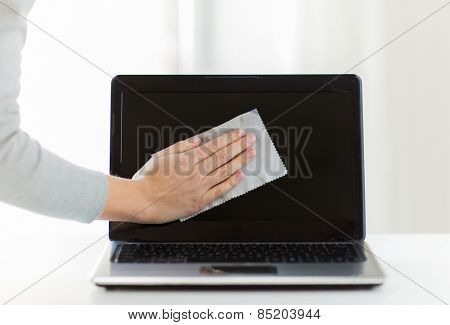 people, housework, electronics and housekeeping concept - close up of woman hand cleaning laptop computer screen with cloth