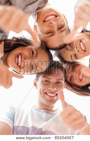 summer holidays and teenage concept - group of smiling teenagers looking down and showing thumbs up