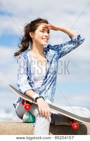 summer holidays and teenage concept - teenage girl with skate outside