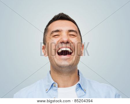happiness, emotions and people concept - laughing man over gray background