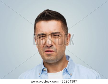 emotions, facial expression and people concept - man wrying of unpleasant smell over gray background