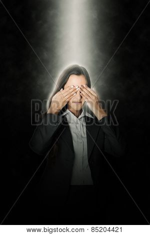 Young businesswoman standing covering her eyes in a ray of light from above as she attempts to block out her surroundings to visualise a project