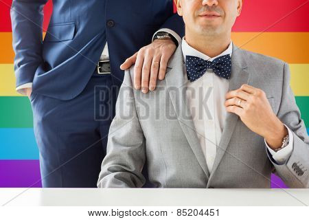people, celebration, homosexuality, same-sex marriage and love concept - close up of male gay couple with wedding rings on putting hand on shoulder over rainbow flag background
