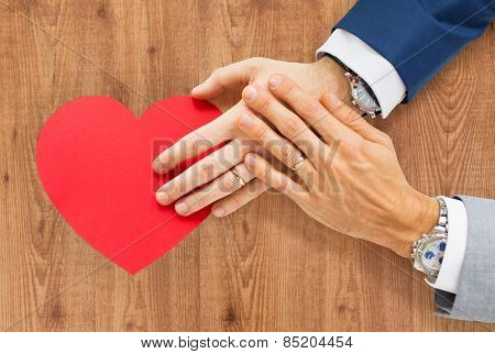 people, homosexuality, same-sex marriage, valentines day and love concept - close up of happy married male gay couple hands with red paper heart shape over wooden background