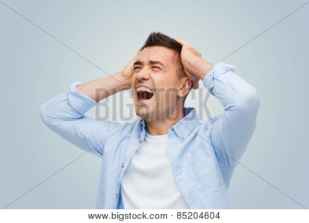 stress, headache, desperation, grief and people concept - unhappy man with touching his head and screaming over gray background