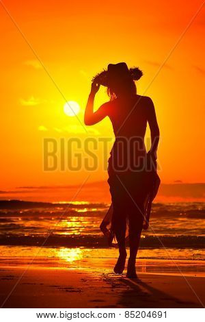 young woman silhouette on the beach in summer sunset light
