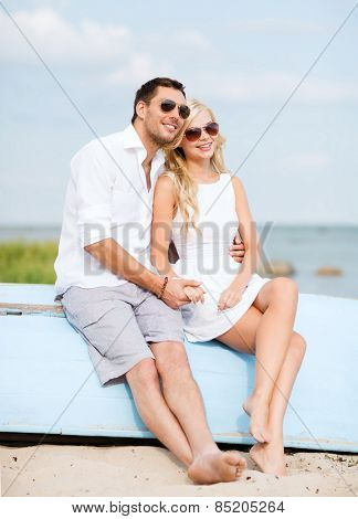 summer holidays and dating concept - couple in shades sitting at sea side